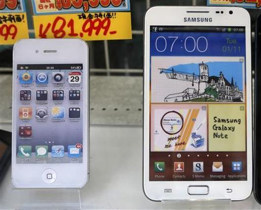 Apple's iPhone, left, and 5.3-inch Samsung Galaxy Note are displayed at a shop.