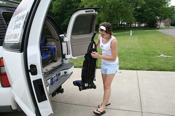 Lacie Baldwin removes a vacuum cleaner from Chevrolet Suburban in Lawrenceburg, Indiana, United States.