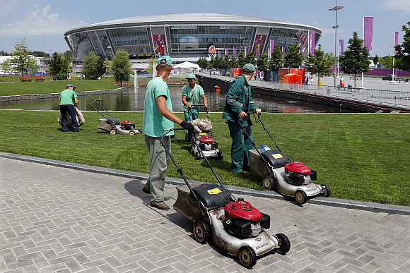 Workers cut the grass around the Donbass Arena stadium in Donetsk, Ukraine.