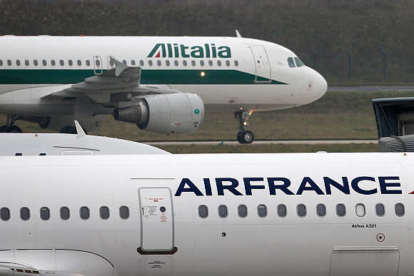 An Alitalia plane passes an Air France plane on the tarmac of Charles de Gaulles International Airport in Roissy near Paris.