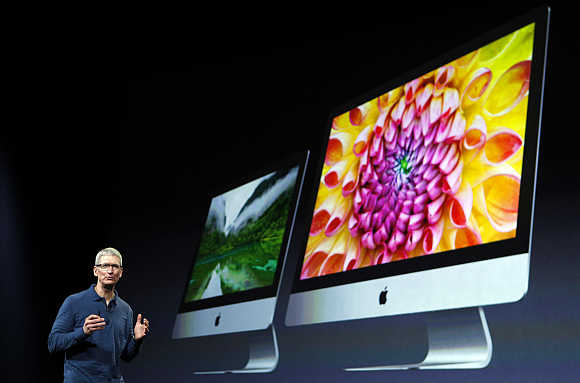 Apple CEO Tim Cook describes models of the iMac desktop computers during an event in San Jose, California.