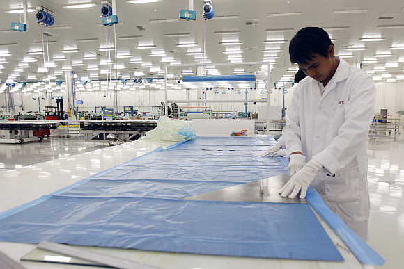 An operator cuts through a sheet of carbon fiber at Strata, a composite aerostructures manufacturing plant, in Abu Dhabi, UAE.