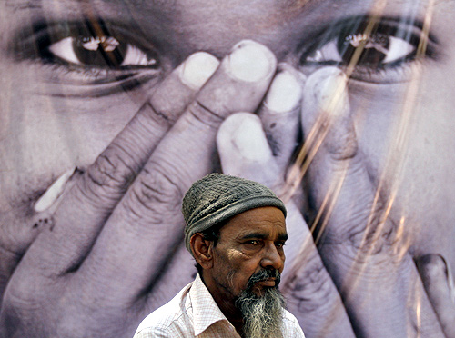 A survivor stands in front of a poster during a photo-exhibition held to commemorate the 10th anniversary of Godhra riots.