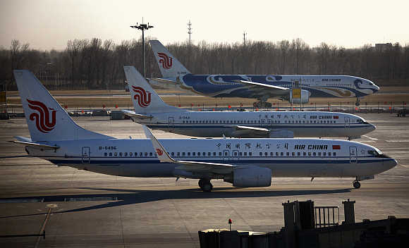 Air China planes pass each other on tarmac and runway at Beijing International Airport.