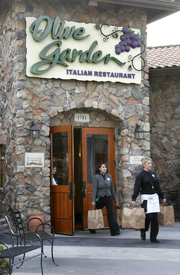 An Olive Garden employee helps a customer carry an order of food to her car at an Olive Garden restaurant in Burbank, California, United States.