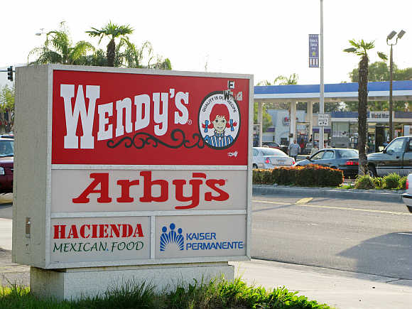 A combined Wendy's/Arby's sign is shown near a restaurant in Fontana, California, United States.