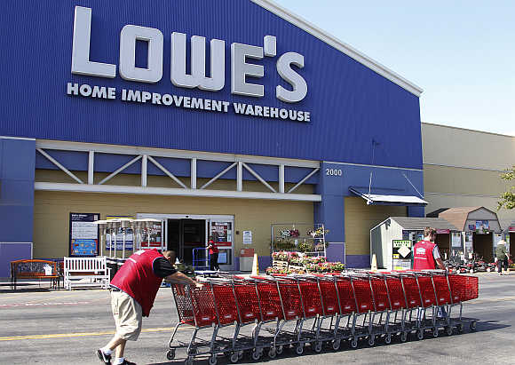 Lowe's workers collect shopping carts at the Lowe's Home Improvement Warehouse in Burbank, California, United States.