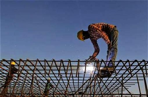 A worker welds iron rods at a construction site in Ahmedabad.