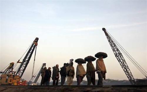 Labourers arrive for work at a railway yard in Chandigarh.