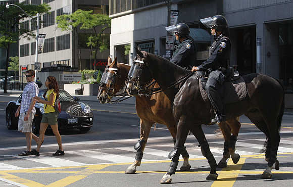Mounted police patrol the financial district of Toronto.