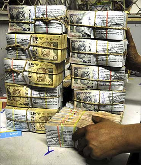 A bank employee carries bundles of rupee notes.