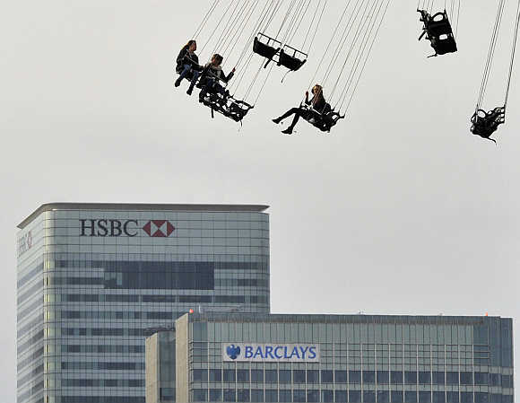 Financial offices of Canary Wharf are seen behind visitors to the O2 arena enjoying a fairground ride in east London.