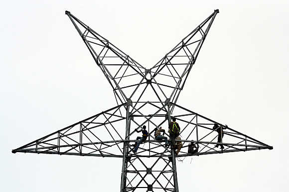 Workers install cables on electric pylon in Ahmedabad.