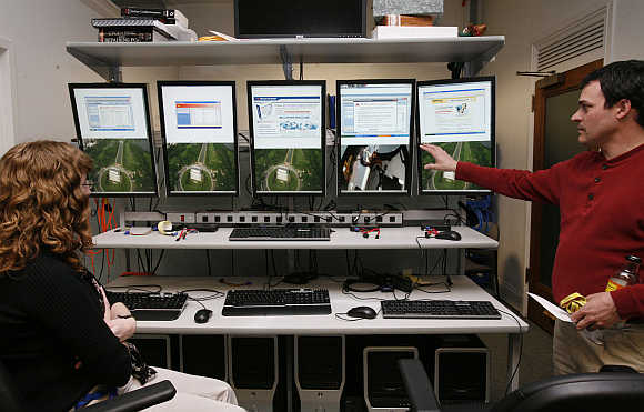 Investigators with the US Federal Trade Commission look at computer monitors in the FTC Internet lab where cyber crime investigations take place in Washington, DC.