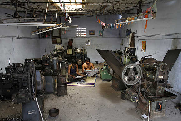 Workers at a small scale factory read newspapers during a power cut in Coimbatore.