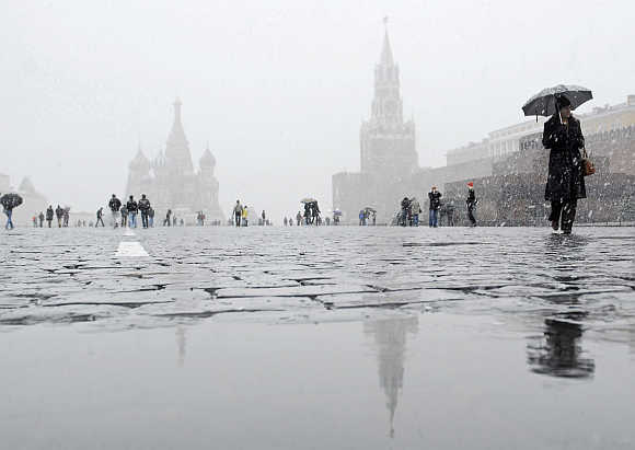 People walk across Red Square during snow in Moscow, Russia.
