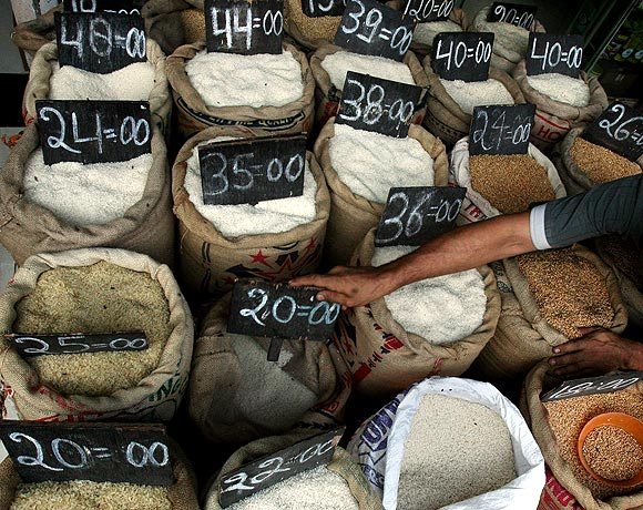 A shopkeeper arranges signs with prices on bags of rice at a shop in Mumbai.