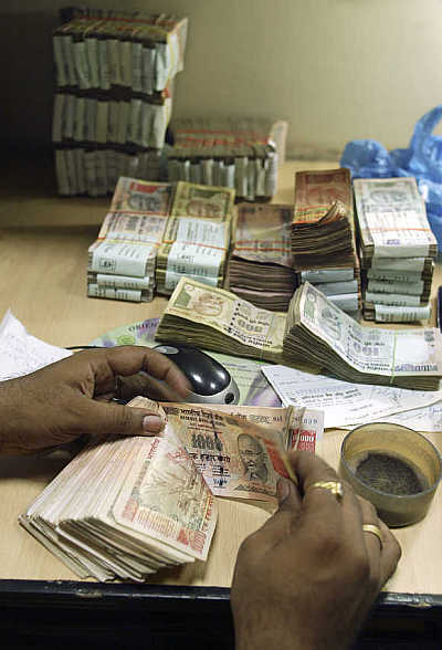 A cashier counts rupee notes inside a bank in Amritsar.