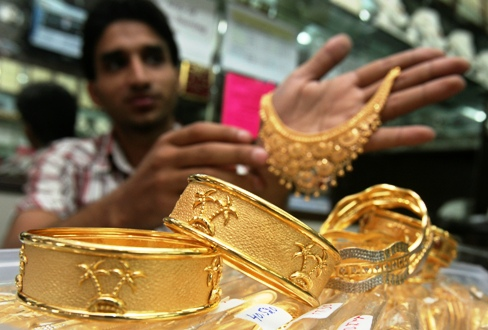 A salesman displays gold ornaments at a jewellery showroom in Chandigarh.