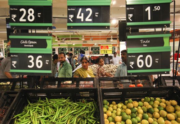 Prices for various vegetables are displayed as people shop in the fresh foods section of a supermarket.