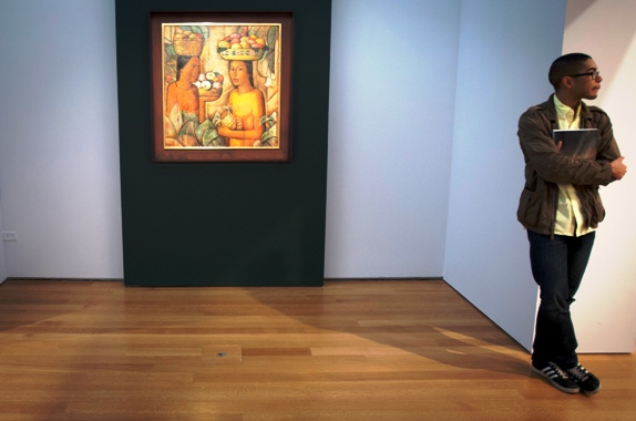 An employee waits beside Ramos Martinez's 'Women with Fruit' at Christie's Auction House in New York.