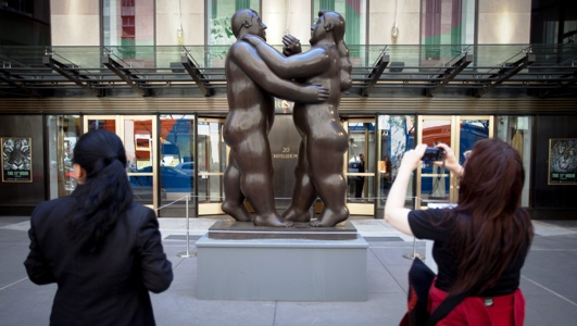 Fernando Botero's 'Dancers' is photographed by a passer-by as it sits in front of Christie's Auction House in New York.
