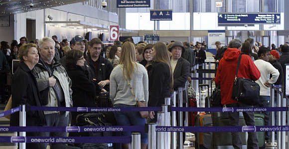 People wait in line at an American Airlines ticket counter at O'Hare International Airport in Chicago.