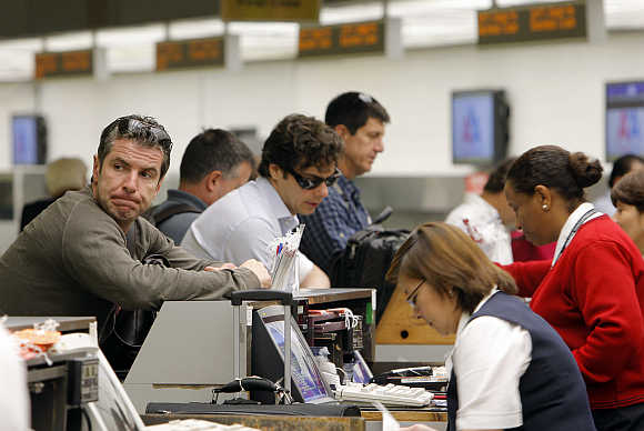 A man waits as he checks in at an American Airlines counter in Miami's International airport.