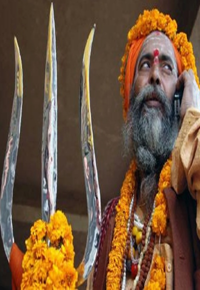 A holy man, is seen talking on a mobile phone in Varanasi.