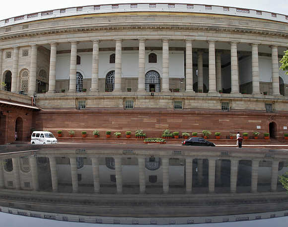 Parliament building is reflected on a car in New Delhi.