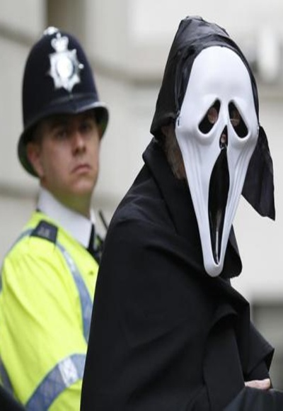 A demonstrator protesting against the upcoming G8 summit, being held near Enniskillen, Northern Ireland, wears a mask outside BAE systems headquarters in central London.