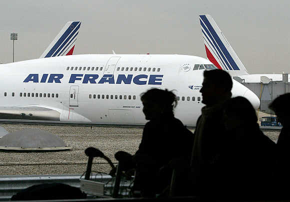Travellers push their bags on a trolley between terminals at Roissy Airport north of Paris.