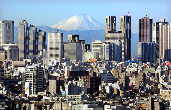 Mt Fuji, covered with snow, is seen through Shinjuku skyscrapers in Tokyo.