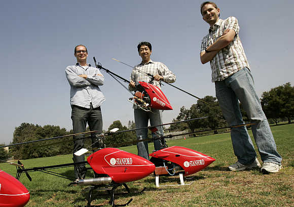Stanford University doctoral students Peter Abbeel, left, and Adam Coates, right, are joined by computer science professor Andrew Ng prior to an air-show of robotic helicopters on the Stanford campus in Palo Alto, California.