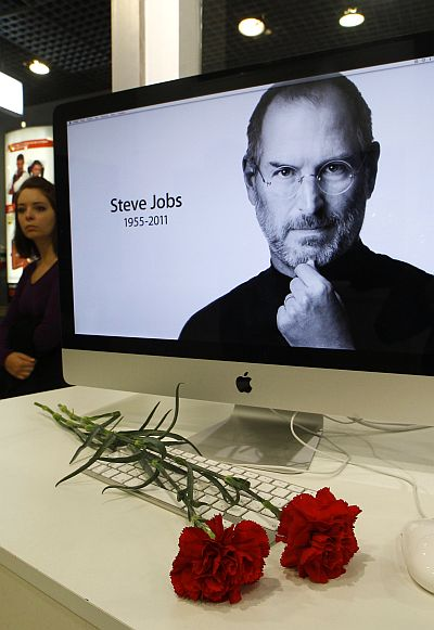 Carnations are placed before a computer screen showing a portrait of Apple co-founder and former CEO Steve Jobs at an Apple store in St. Petersburg.