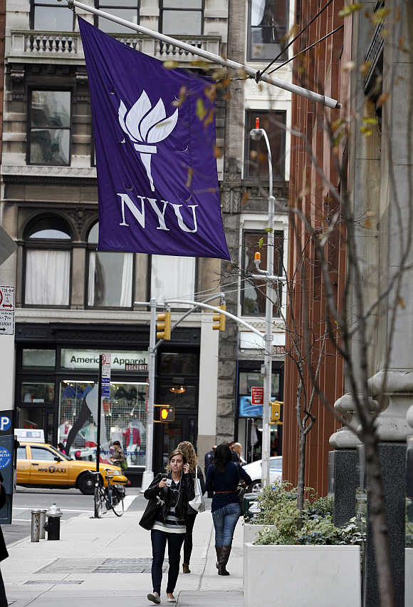 Students walk down the street at New York University in New York.
