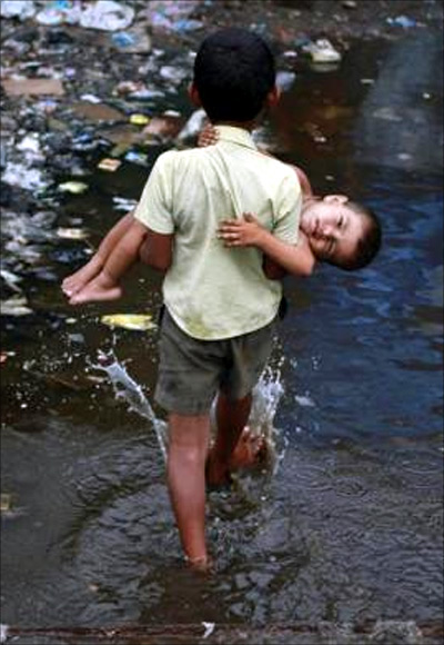 Ashfaq carries his two-year-old brother Farhaan through a flooded pathway in a Mumbai slum.