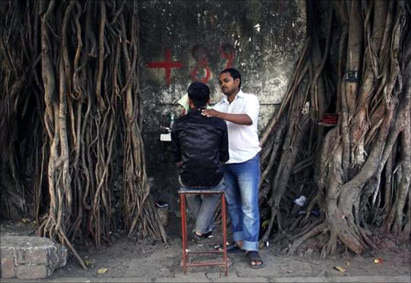 A man gets a shave by a roadside barber in a slum area in Mumbai.
