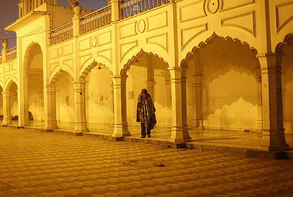 A homeless man wrapped in a blanket walks inside a Sikh temple compound on a cold winter night in New Delhi.