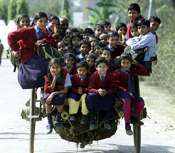 Children ride in a cart on the way home from school on the outskirts of New Delhi.