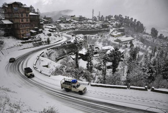 Vehicles drive down a snow-covered road after heavy snowfall in Shimla.