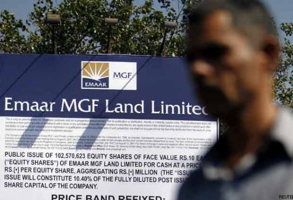 A man walks past a billboard displaying Initial Public Offering details for Emaar MGF Land.