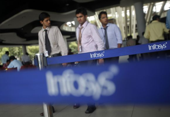 Employees of Indian software company Infosys walk past Infosys logos at their campus.