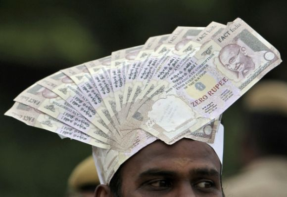 A supporter of veteran Indian social activist Anna Hazare wears a cap lined with fake currency notes while attending a public meeting by Hazare.