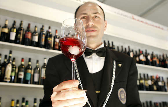 A sommelier tests a glass of red wine during the Vinitaly wine expo in Verona, Italy.