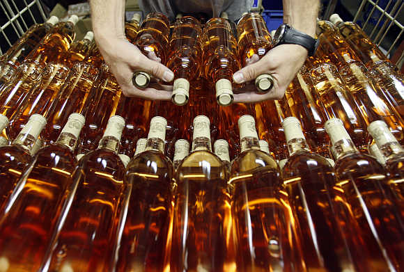 A worker prepares bottles of rose wine at the Domaine Saint Andre de Figuiere at La Londe Les Maures in Provence, France.