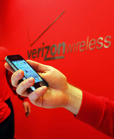 An employee holds out an iPhone for a customer at a Verizon store in Boston, Massachusetts.