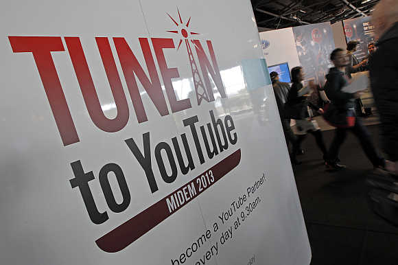 Visitors walk past a YouTube stand during the International Record Music Publishing and Video Music Market in Cannes, France.