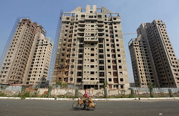 A man cycles past residential buildings under construction in Kolkata.