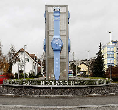 Cars drive past a giant Swatch watch placed in the centre of a roundabout in Grenchen, Switzerland.